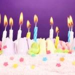 pastel de cumpleaños con velas sobre fondo violeta — Foto de Stock   #10811621