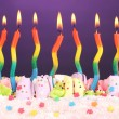 Birthday cake with candles on violet background — Stock Photo #10811630