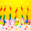 Birthday cake with candles on yellow background — Stock Photo