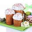 Beautiful Easter cakes, colorful eggs in basket and flowers isolated on white - Stock Photo
