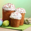 Beautiful Easter cakes, colorful eggs and pussy-willow twigs on wooden table on green background - Stock Photo