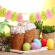 Beautiful Easter cakes, colorful eggs in basket and candles on wooden table on yellow background - Stock Photo