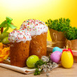 Beautiful Easter cakes, colorful eggs and candles on wooden table on yellow background - Stock Photo
