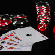 Four of a kind with poker chips and dice on black background — Stock Photo