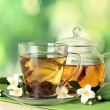 Green tea with jasmine in cup and teapot on wooden table on green background - Foto Stock