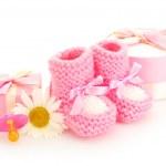 Pink baby laarzen, fopspeen, geschenken en bloem geïsoleerd op wit — Stockfoto