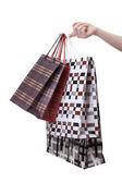 Feminino mão segurando sacolas de compras brilhantes isoladas no branco — Fotografia Stock