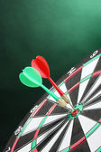 Dart board with darts on green background — Stok fotoğraf