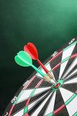 緑色の背景でダーツとダーツボード — ストック写真