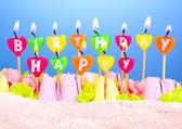 Pastel de cumpleaños con velas sobre fondo azul — Foto de Stock