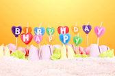 Pastel de cumpleaños con velas sobre fondo amarillo — Foto de Stock