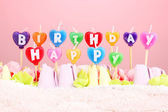 Birthday cake with candles on pink background — Stock Photo