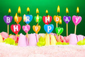 день рождения торт с зажженными свечами на зеленом фоне — Стоковое фото