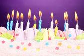 Födelsedagstårta med ljus på violett bakgrund — Stockfoto