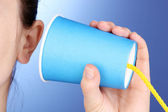 Human ear and paper cup near it close-up on blue background — Stock Photo