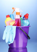 Bucket with cleaning items on blue background — 图库照片