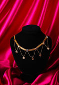 Beautiful golden necklace on mannequin on red silk fabric — Stock Photo