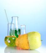 Genetically modified fruits on blue background — Stock Photo