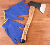 Axe and gloves on wooden background — Zdjęcie stockowe