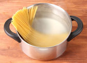 Cook the spagetti in the pan on wooden background close-up — Stock Photo
