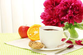Cup hot chocolate, apple, orange, cookies and flowers on table in cafe — Stock Photo