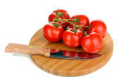 Fresh tomatoes and knife on wooden board isolated on white — Stock Photo