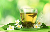 Cup of green tea with jasmine flowers on wooden table on green background — Stock Photo
