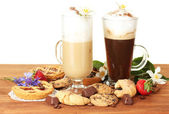 Glasses of coffee cocktail on wooden table with sweet and flowers on white background — Stock Photo