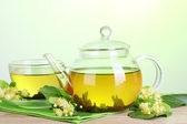Teapot and cup with linden tea and flowers on wooden table on green background — Stock Photo