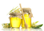 Jars with linden honey and flowers isolated on white — Stock Photo
