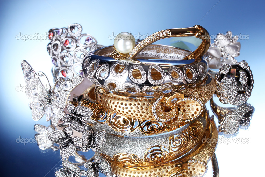 Beautiful silver and gold bracelets and rings on blue background — Stock Photo #10812827