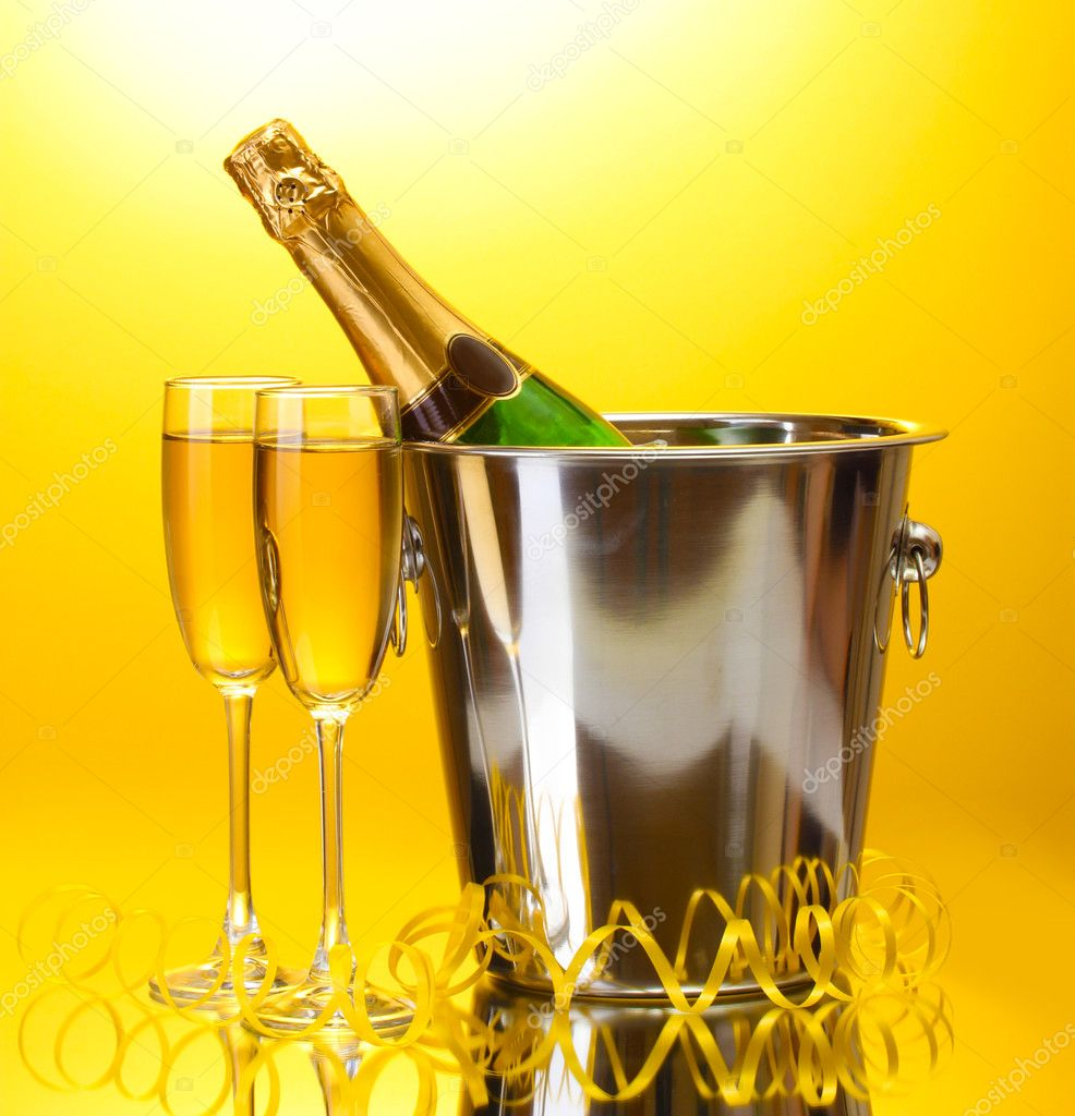 Champagne bottle in bucket with ice and glasses of champagne, on yellow background — Stock Photo #10812861