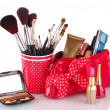 Red glass with brushes and makeup bag with cosmetics isolated on white — Stock Photo #10821620