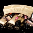 Beautiful golden makeup bag and cosmetics isolated on black — Stock Photo #10821759