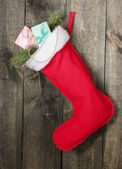 Meia de natal com presentes no plano de fundo de madeira — Foto Stock