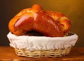 Pečený chleba v koši na dřevěný stůl na hnědé pozadí — Stock fotografie