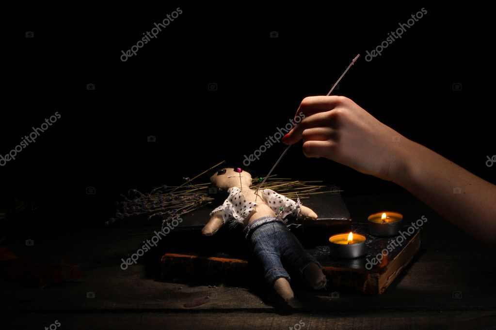 Voodoo doll boy pierced by a needle on a wooden table in the candlelight — Stock Photo #10828468