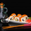 Tasty rolls served on white plate with chopsticks and soy sauce isolated on black — Stock Photo