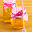 Jars of honey and wooden drizzler on yellow honeycomb background — Stock Photo #10891325