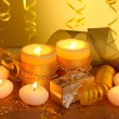 Stock Photo: Beautiful candles, gifts and decor on wooden table on yellow background