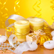Beautiful candles, gifts and decor on wooden table on yellow background — Stockfoto