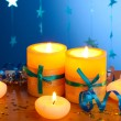 Beautiful candles, gifts and decor on wooden table on blue background — Stock Photo #10895583