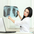 Beautiful girl doctor holding X-ray in the office — Stock Photo #10896054