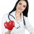 Young beautiful doctor with stethoscope holding heart isolated on white — Stock Photo