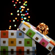 Open gift box with bokeh background on black — Stock Photo