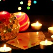 Candles and playing cards on wooden table on bright background — Stock Photo