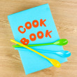 Cookbook and kitchenware on wooden background — Stock Photo