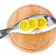Royalty-Free Stock Photo: Fresh fish with lemon on wooden cutting board isolated on white