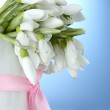 Beautiful bouquet of snowdrops in vase with bow on blue background — Stock Photo #10898421