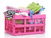 Clothes in pink plastic basket isolated on white — Stock Photo